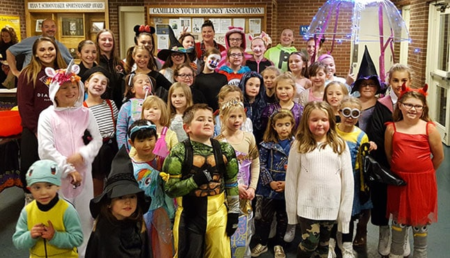 Skaters, Coaches and Board Members dressed up for Halloween posing for a photo
